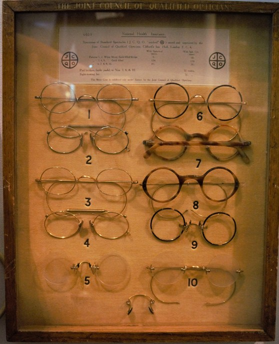 Colour photograph of a display case showing various styles of NHS spectacles