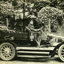 Black and white photograph of an early Renault motor car with chauffeur from the early twentieth century