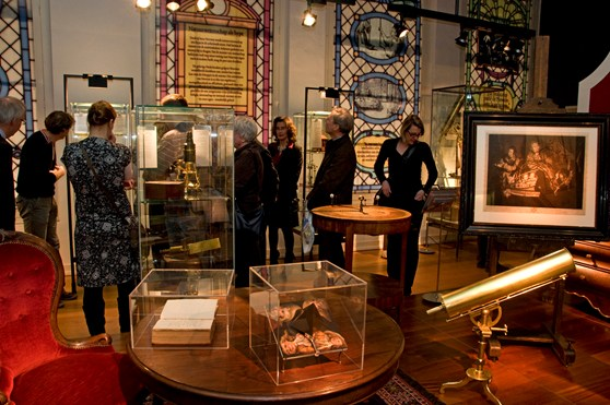 Colour photograph of a group of visitors walking through an exhibition of old scientific instruments