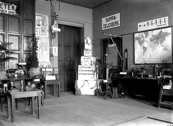 Black and white photograph of a small exhibition of scientific objects within a physics laboratory