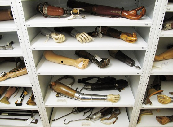 Colour photograph of a number of prosthetic arms in museum storage shelves