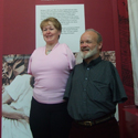 Colour photograph of a male and a female thalidomide patient standing in front of an exhibition display wall
