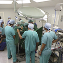 Colour photograph of a simulation based reenactment of a surgical procedure carried out by numerous medical staff