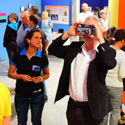 Colour photograph of museum goers using hand held viewing devices within an exhibition of colour