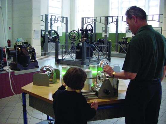 Colour photograph of museum goers using experimentation devices within a museum exhibition on energy