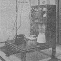 Black and white photograph of a Japanese living room with electricity cables connecting from the light fitting to various electrical devices
