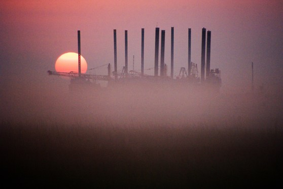 Colour photograph of a sunrise over an oilfield in Texas North America