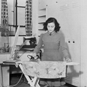 Black and white early twentieth century photograph of a woman ironing