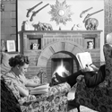 Black and white photograph of a husband and wife sat in front of their living room fire