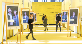 Colour photograph of visitors inside a large gallery space with photographs displayed on easels