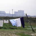 Colour photograph of laundry hanging out to dry with a nuclear power station in the far background