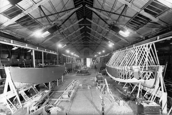 Black and white photograph of a large warehouse with two partially constructed boats