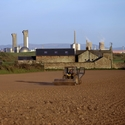 Colour photograph of a field being ploughed with a nuclear power station in the background