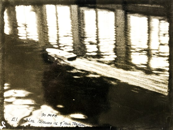 Black and white photograph of a model boat travelling at speed in a water tank testing facility