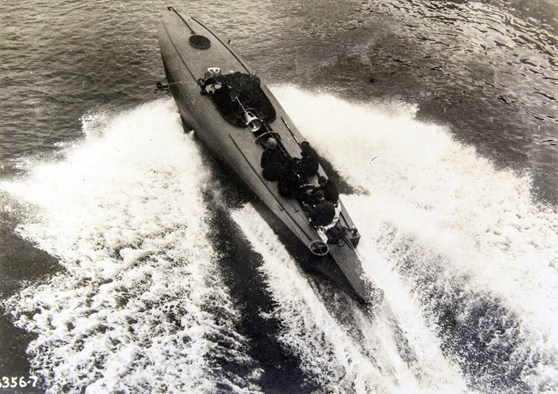 Black and white photograph of a coastal motor boat travelling at speed
