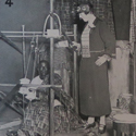 Black and white photograph of a Nigerian worker seated and a loom and European woman observing