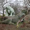 Colour photograph of two concrete Iguanadon models from the nineteenth century in different states of repair