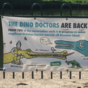 Colour photograph of a poster informing public that conservation work will be carried out on the concrete dinosaurs