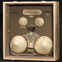 Glass display case containing various nineteenth century cosmetic devices two cheek plumpers eyebrows patches and two breast pads