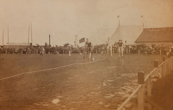 Sepia photograph of cyclists on high wheeler bicycles during a race with spectators in the background from late nineteenth century