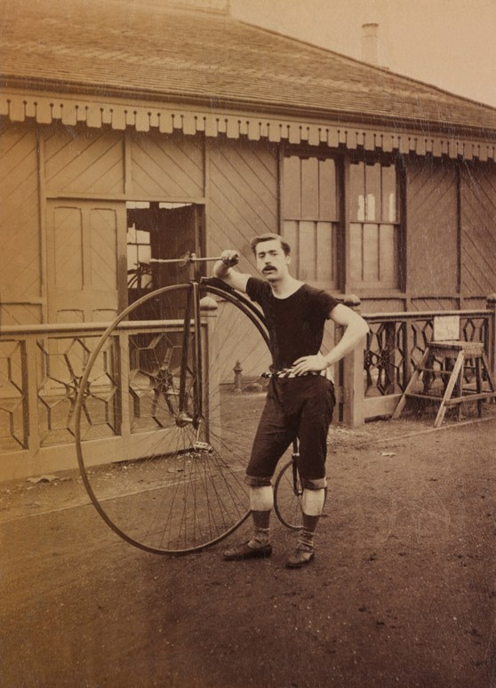 Sepia photograph of a cyclist with his high wheeler bicycle from the late nineteenth century