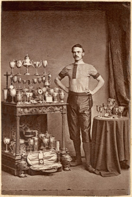 Sepia photograph of a cyclist with a case of trophies from the late nineteenth century
