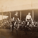 Sepia photograph of two cyclists on high wheeler bicycles at the start line of a race with spectators in the background from late nineteenth century