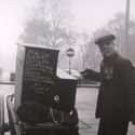 Black and white photograph of a street organ grinder on display in the exhibition