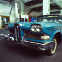 Colour photograph of a blue Ford Edsel car on display in a gallery