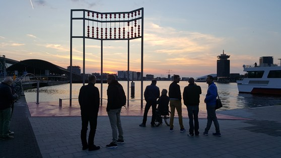 Colour photograph of evening visitors to an AIDS monument in Amsterdam