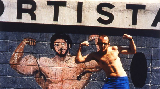 Video still featuring a man posing in front of a bodybuilder illustration on an outside wall